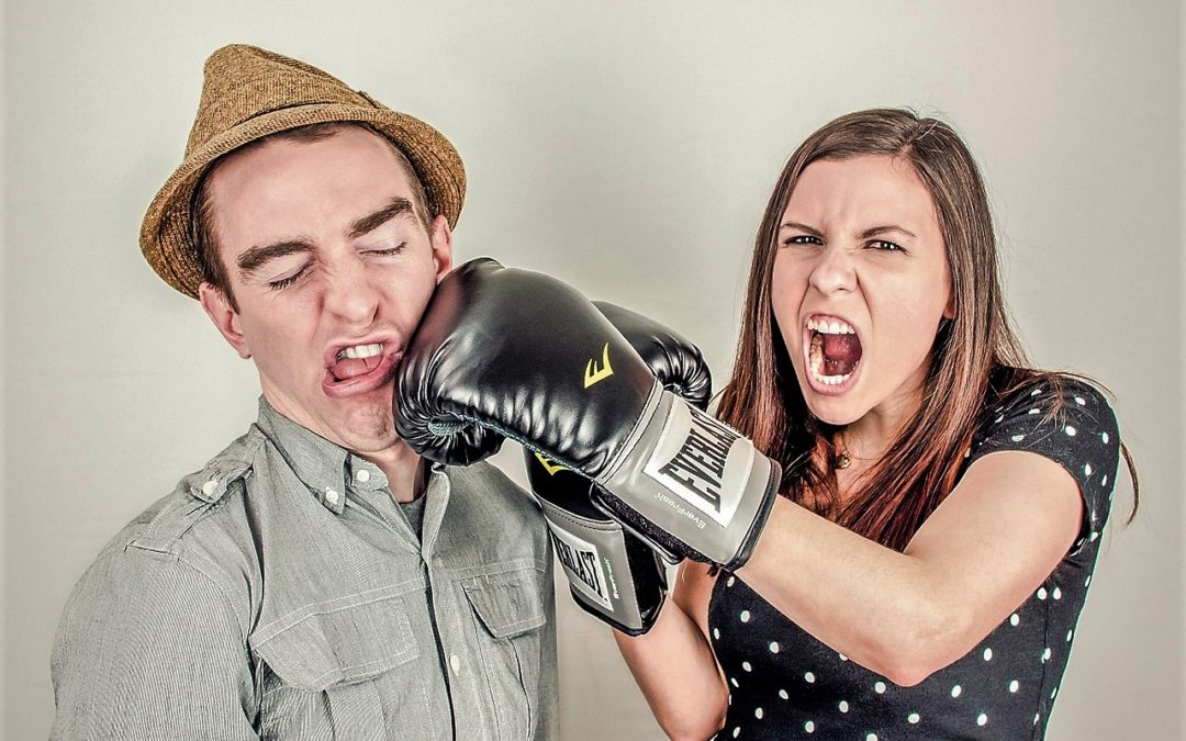 Angry woman in boxing gloves punching man in hat as illustration for should you stay together for the sake of the kids
